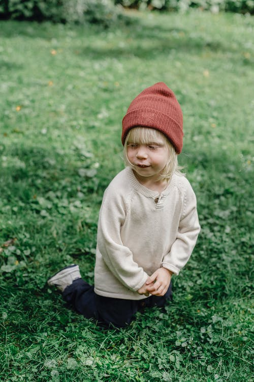 From above full body of calm kid wearing trendy hat looking away while sitting on grassy meadow in street on blurred background