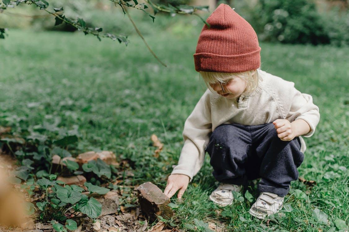 Kind In Oranje Gebreide Muts En Bruine Jas Zittend Op Groen Gras