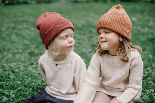 Mädchen Im Weißen Langarmhemd Und In Der Roten Strickmütze, Die Auf Grünem Grasfeld Während Sitzen