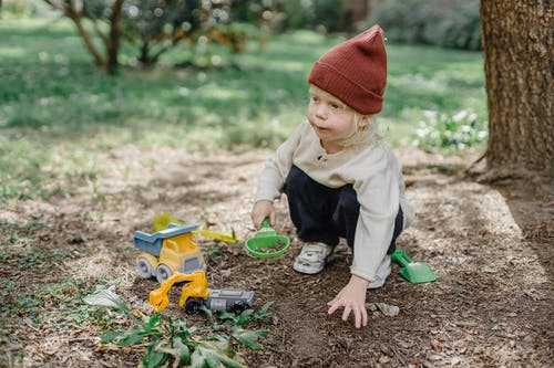 Cute little child playing with toys in yard