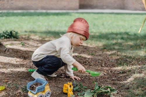 Niño En Suéter Marrón Y Pantalones Vaqueros Azules Jugando Con Bloques De Juguete De Plástico Amarillo Y Rojo