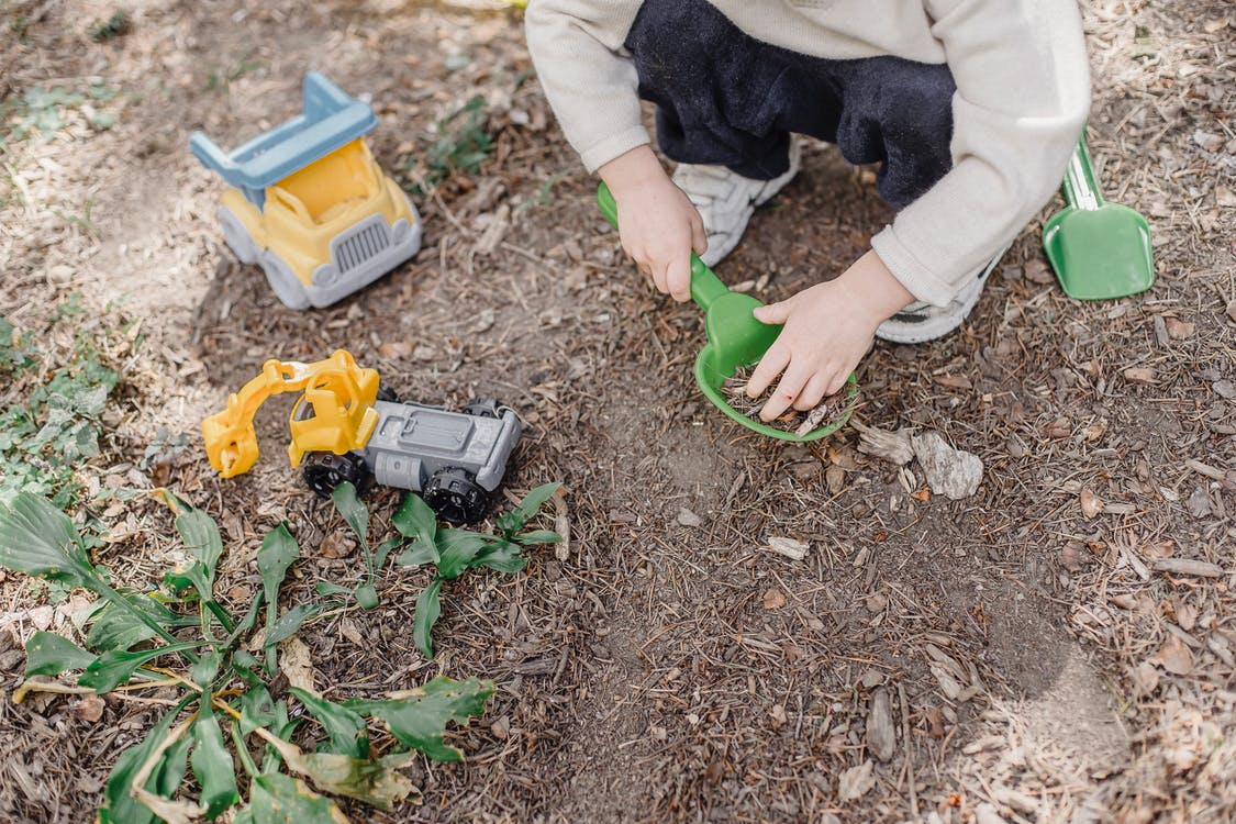 Little kid playing in garden with toys