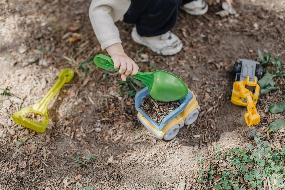 Unrecognizable little child playing with plastic toy car and shovel in calm sunny yard