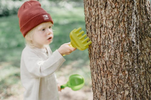 High angle of focused little blond boy in casual wear and brown hat rubbing tree trunk with toy rake in garden