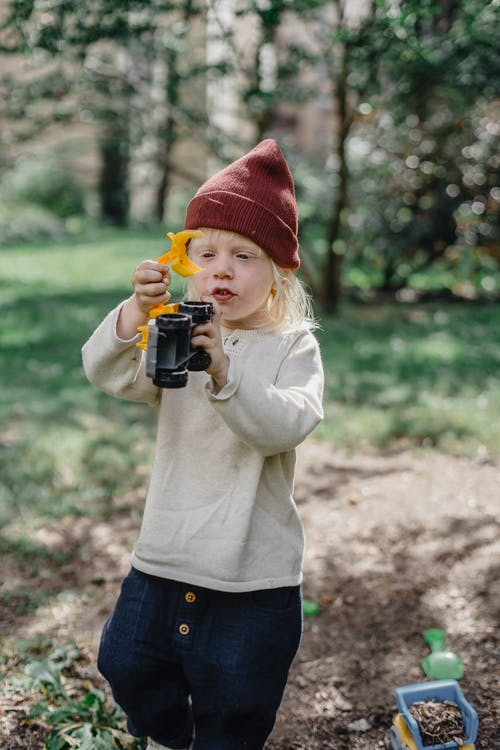 Little blond boy in casual clothes and brown hat playing with toy binoculars in garden in sunny day