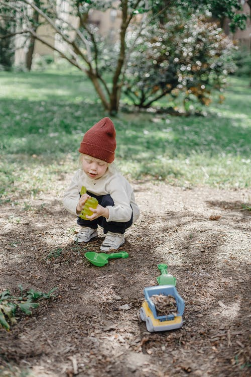 Little kid playing with toys in summer garden