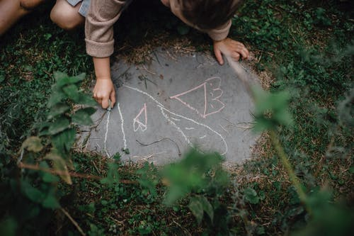 High angle of unrecognizable child drawing with chalks on small piece of concrete block in grassy yard