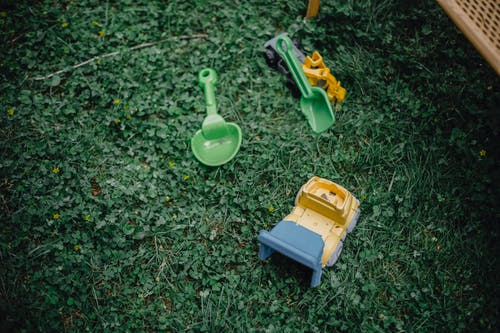 High angle of green grass and colourful plastic kids toys on garden meadow