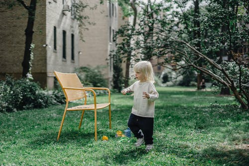 Full body of adorable little boy in stylish outfit walking on grassy lawn near yellow chair in backyard on sunny day