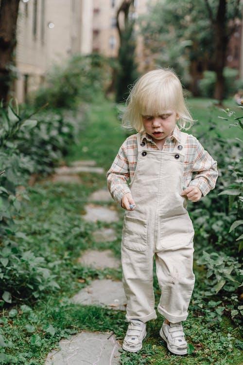 Cute stylish child standing in green park near lush plants