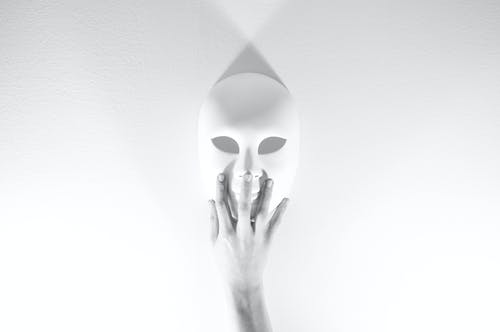 Person Holding White Mask in Grayscale Photography