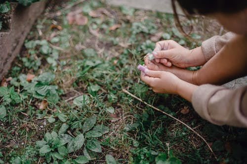 Unrecognizable child painting feet nails with chalks in garden