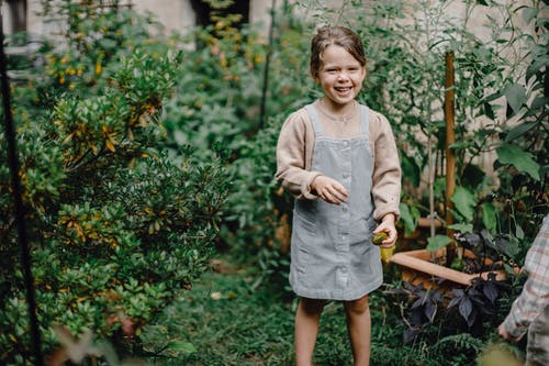 Cheerful little girl in stylish outfit smiling while standing in garden amidst lush green shrubs with picked fruit in hand