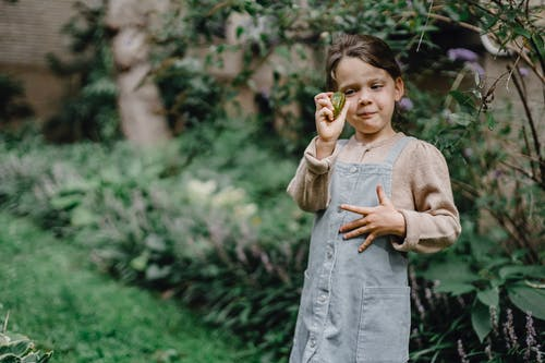 Funny kid holding ripe fruit in hand while resting in green garden