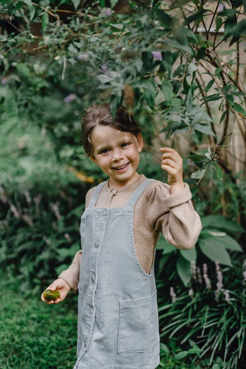 Happy little girl in casual outfit smiling and looking at camera while resting in lush green garden during holidays