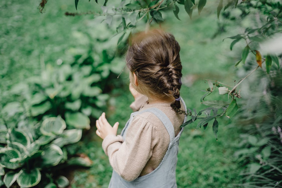 Side view of unrecognizable stylish little girl standing on grassy lawn near fresh green plants while resting in countryside during holidays
