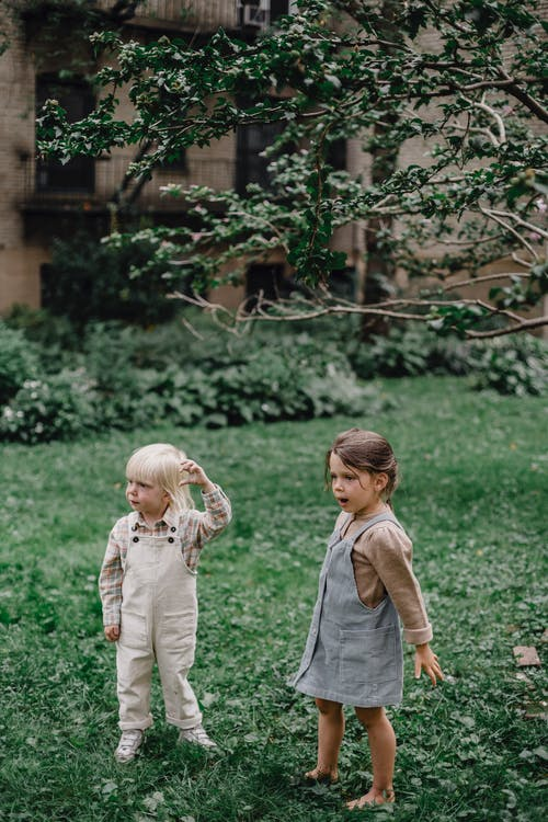 Boy in Gray Long Sleeve Shirt and Girl in White Long Sleeve Shirt Walking on Green
