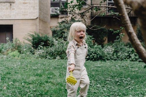 Meisje In Wit En Grijs Shirt Met Lange Mouwen Gele Plastic Fles Te Houden
