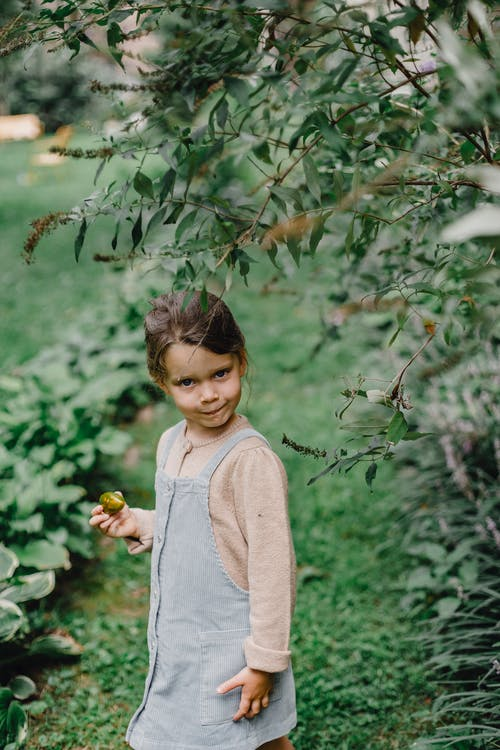 Girl in Beige Long Sleeve Shirt Standing Under Green Tree