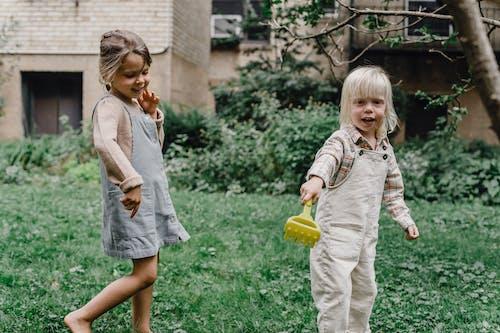 Meisje In Witte Jurk Met Gele Plastic Beker Staande Op Groen Grasveld