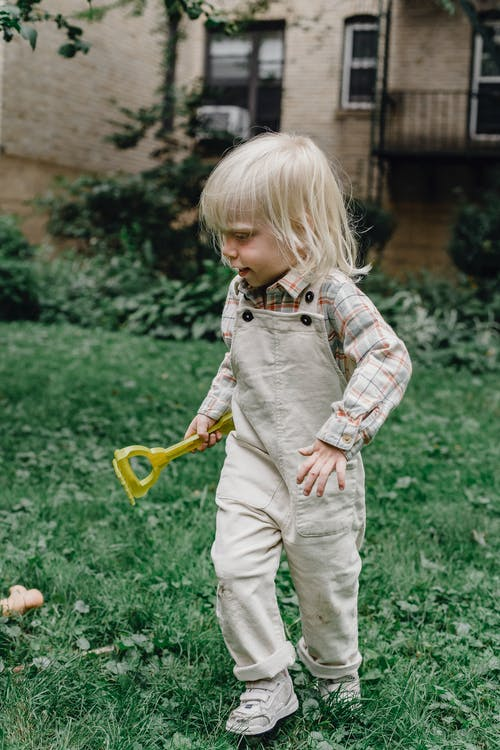 Curious little boy in trendy outfit with plastic rake