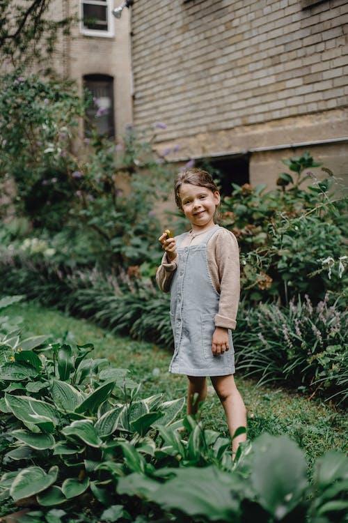 Girl in Gray Long Sleeve Shirt Standing on Green Grass Field