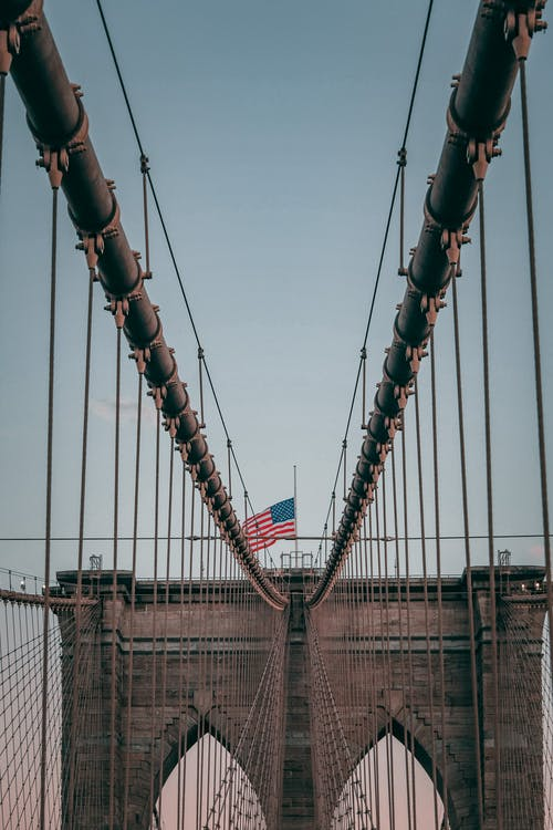 Top of famous suspension Brooklyn Bridge with American flag under cloudless blue sky