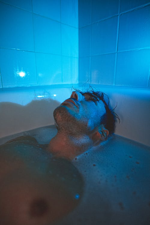 Adult man lying in bathtub full of water and looking up in dark blue light