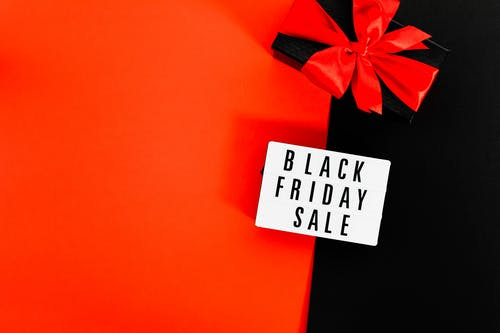 A Black Friday Sale Signage and Black Box Tied With Red Ribbon on Red and Black Background