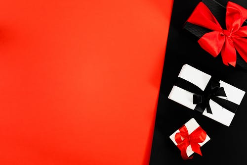 Three Boxes Tied With Ribbons on Red and Black Background