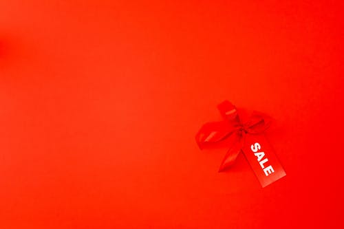 A Red Ribbon and Sale Tag on Red Background