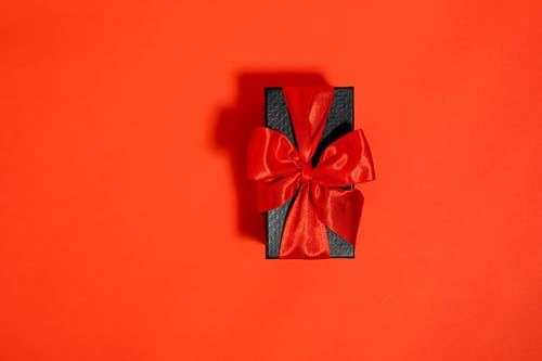 A Black Box Tied With Red Ribbon on Red Background