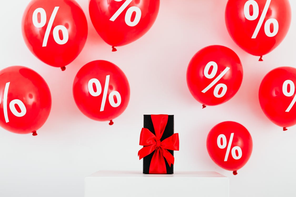 A Gift With Red Ribbon in Between Red Balloons With Percentage Symbols on a White Background