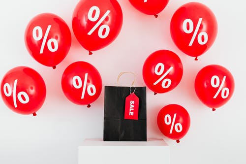 A Black Paper Bag With Sale Tag in the Middle of Red Balloons With Percentage Symbols on White Background