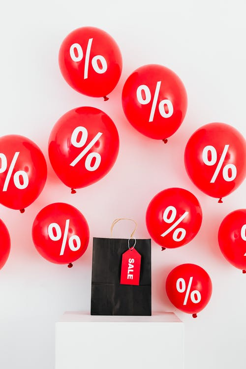A Black Paper Bag With Sale Tag in the Middle of Red Balloons With Percentage Symbols