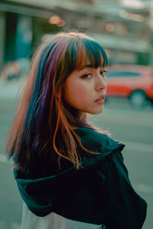 Back view of confident Asian teenage lady with colorful hair in casual outfit standing on city street and looking over shoulder thoughtfully