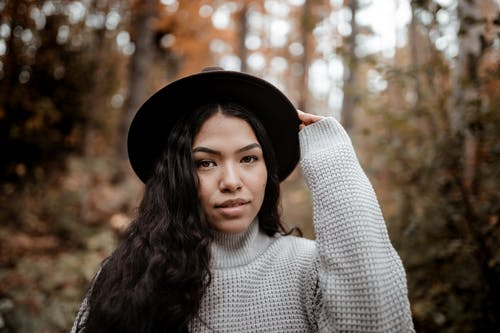 Woman in White Turtleneck Sweater and Black Hat