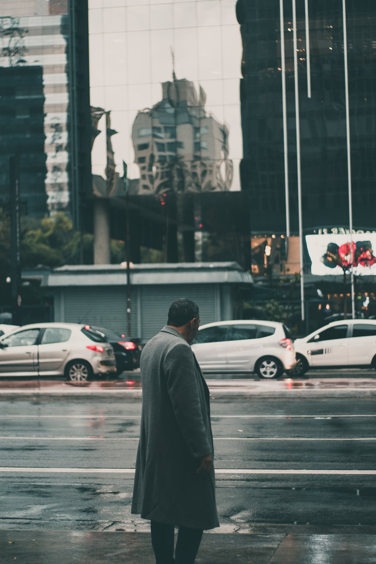 Man Wearing Black Coat Standing on Sidewalk
