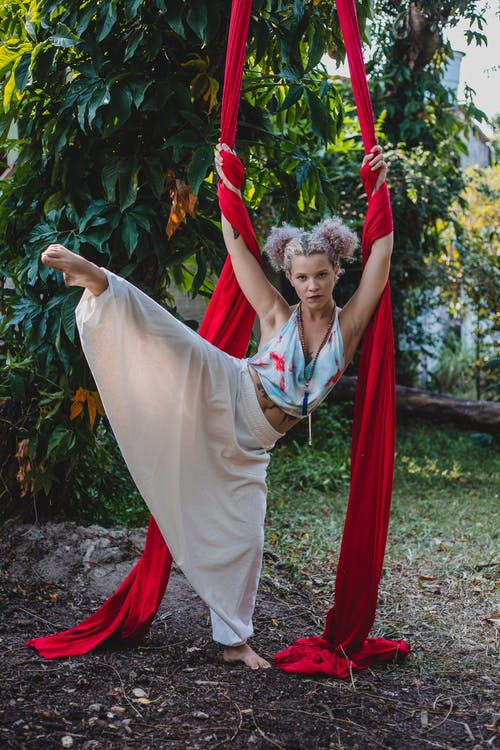 Full body of young confident tattooed female with curly hair in activewear stretching legs while practicing aerial yoga in green park