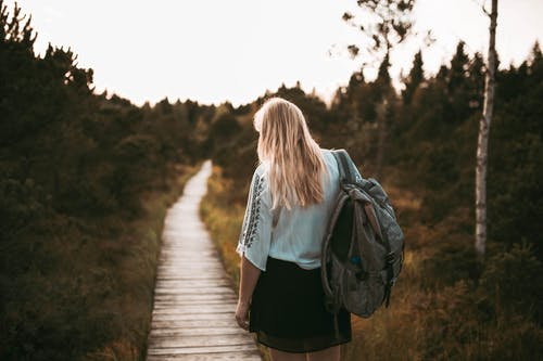 Back of Woman Standing on Pathway Carrying Backpack
