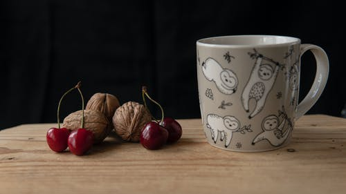 Mug of beverage near whole cherries and walnuts