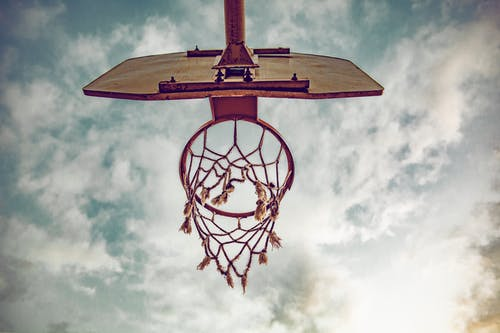 Brown and White Basketball Hoop Under White Clouds and Blue Sky