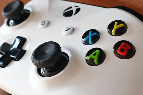White Xbox Game Controller on Brown Wooden Table