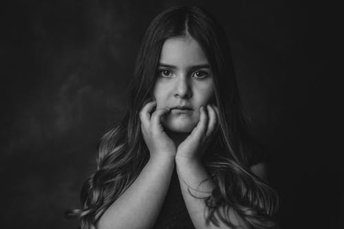 Black and white of cute little girl with long wavy hair touching cheeks and looking at camera against dark background