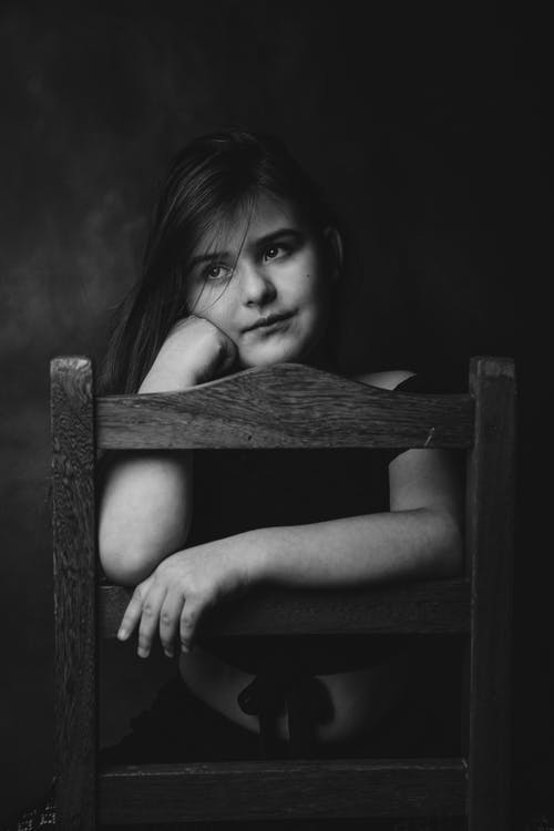 Black and white of dreamy adorable little girl with long hair resting on chair with hand on cheek and looking away pensively