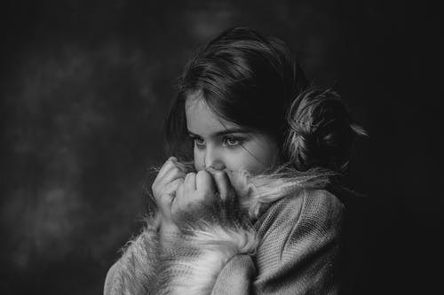Black and white of contemplative kid in stylish outfit covering face while looking away