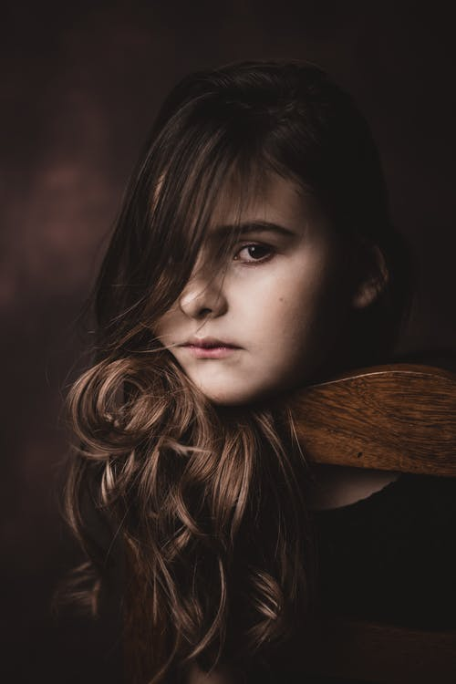 Serious stylish girl with makeup on brown background