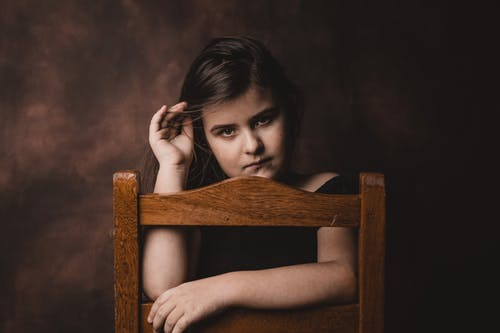 Focused girl in stylish outfit touching hair while sitting on wooden chair and looking at camera on brown background