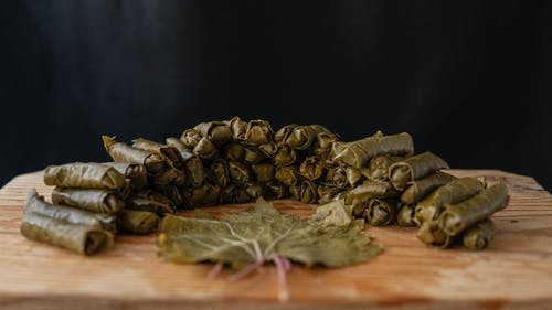 Delicious sarma rolls near vine leaf on wooden cutting board on black background