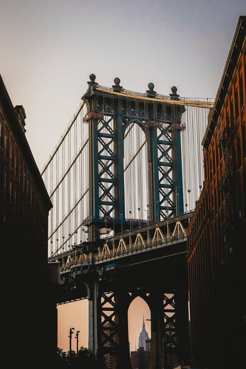 Old Brooklyn Bridge under white sky at sunset